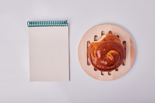 Caucasian style pastry bun on wooden platter with a recipe book aside.