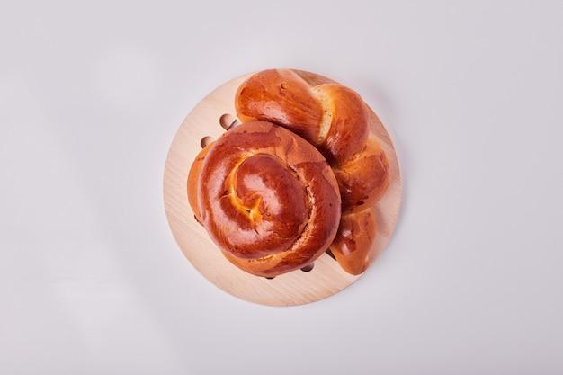 Panini della pasticceria di stile caucasico su un piatto di legno, vista dall'alto.