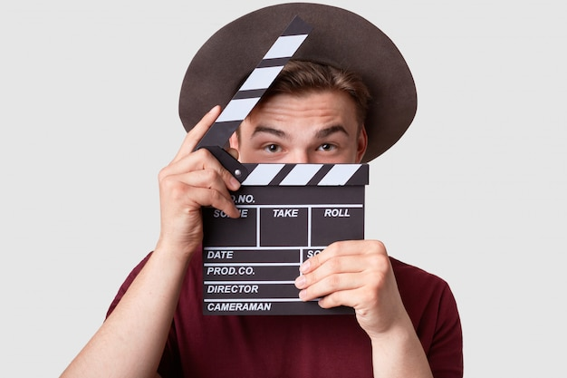 Caucasian successful male producer looks through opened clapperboard
