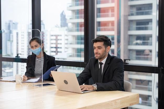 사무실에서 회사 면접 동안 책상에서 아시아 비서 여자와 컨설팅 백인 감독자 사업가