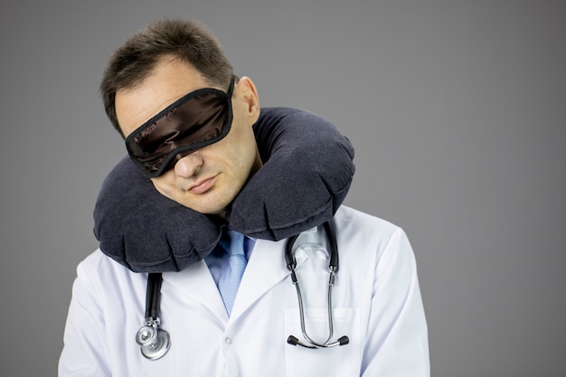 目の上のトラベル枕と睡眠マスクを持つ白人の外科医医師