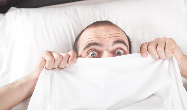 Кавказский удивлен мужчина в постели.