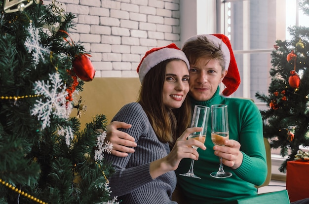Caucasian sweet couple with red santa hat enjoy drinking champagne and looking with christmas tree celebrating in house