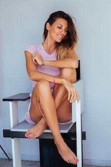 Look casual da donna abbronzata caucasica, pantaloncini rosa e top rosa, tatuato, seduto sulla sedia