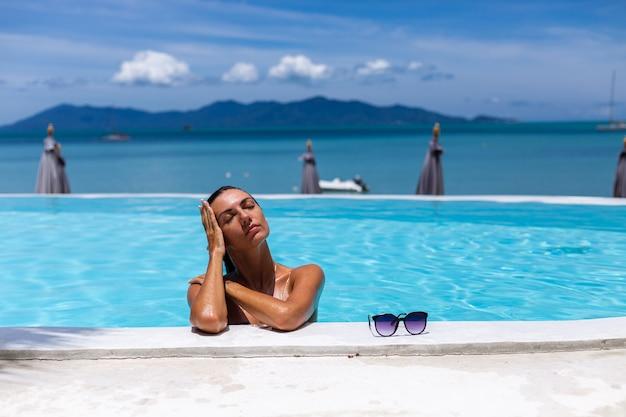 Pelle di bronzo lucida donna abbronzata caucasica da piscina in bikini blu al giorno pieno di sole