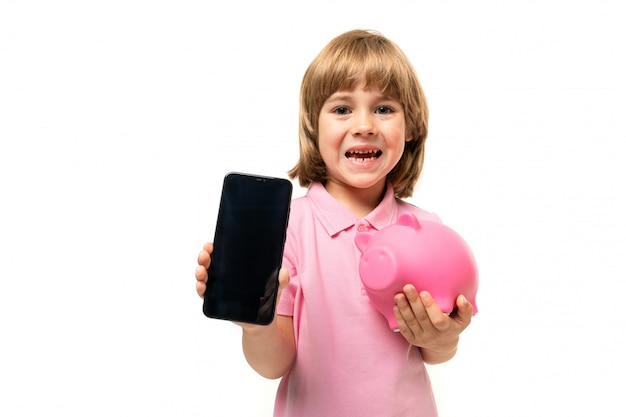 Caucasian teeanger boy holds a phone in one hand and pink pig moneybox in other hand on white wall