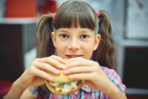 Caucasian teen girl eating hamburger for breakfast at school.