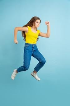 Caucasian teen girl portrait isolated on blue studio wall