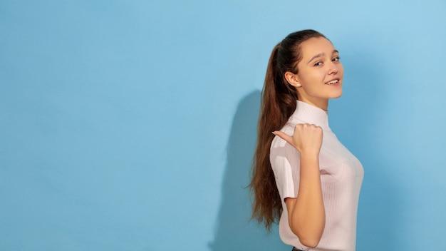 Ritratto teenager caucasico della ragazza isolato su studio blu