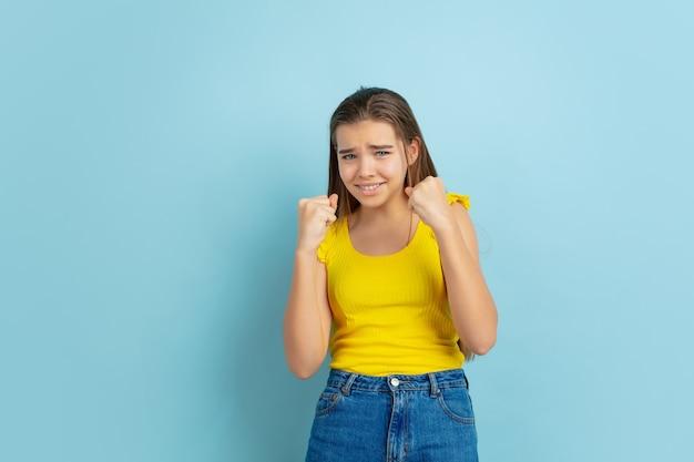 Ritratto della ragazza teenager caucasica isolato su priorità bassa blu. bellissimo modello di capelli lunghi in abbigliamento casual.