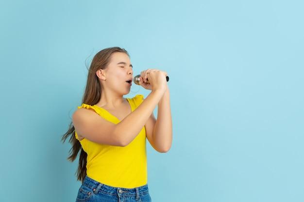 青い背景に分離された白人の十代の少女の肖像画。カジュアルで美しいロングヘアモデル。