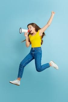 青い背景に白人の十代の少女の肖像画。カジュアルで美しいロングヘアモデル。