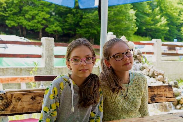 緑の夏の公園のテーブルに座って眼鏡をかけた白人の10代の女の子。