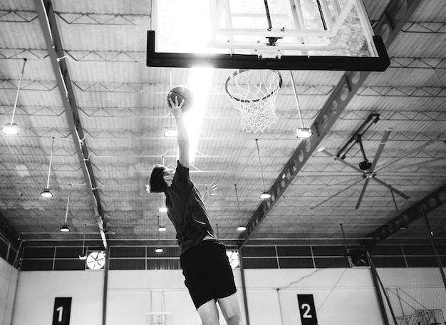 Кавказский подросток играет в баскетбол один на корте