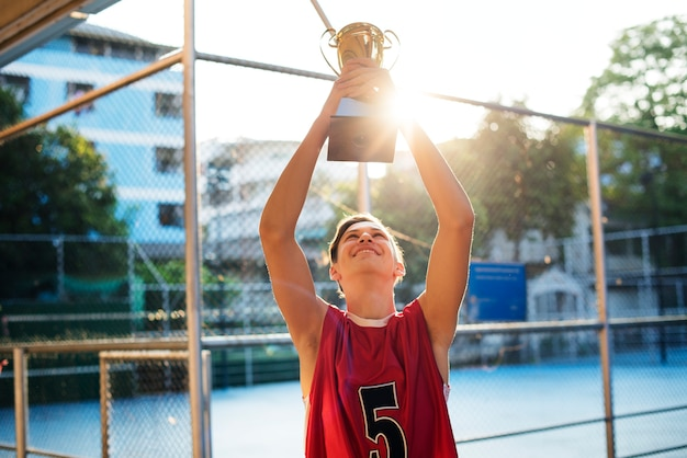 Caucasian teenage boy in sporty clothes holding up a trophy outdoors