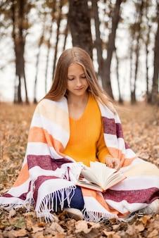 가을 공원에 앉아 책을 읽는 따뜻한 격자 무늬로 덮인 백인 10대 소녀