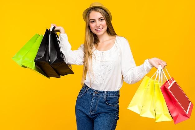 Кавказская девочка-подросток на желтом фоне. стильная молодая женщина с хозяйственными сумками в руках