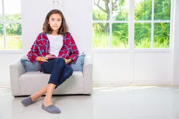 Caucasian teenage girl playing smartphone or tablet pc on sofa at home