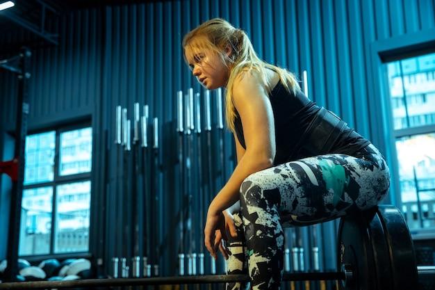 Кавказская девочка-подросток занимается тяжелой атлетикой в тренажерном зале. женская спортивная модель позирует перед тренировкой со штангой, выглядит уверенно. бодибилдинг, здоровый образ жизни, движение и концепция действий.