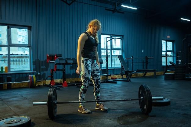 Кавказская девочка-подросток занимается тяжелой атлетикой в тренажерном зале. женская спортивная модель, готовящаяся к тренировке со штангой, выглядит сосредоточенно. бодибилдинг, здоровый образ жизни, движение и концепция действий.