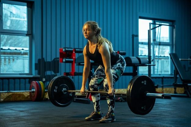 Кавказская девочка-подросток занимается тяжелой атлетикой в тренажерном зале. женская спортивная модель, тренирующаяся со штангой, выглядит сконцентрированной и уверенной. бодибилдинг, здоровый образ жизни, движение и концепция действий.