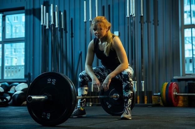Кавказская девочка-подросток занимается тяжелой атлетикой в тренажерном зале. женская спортивная модель