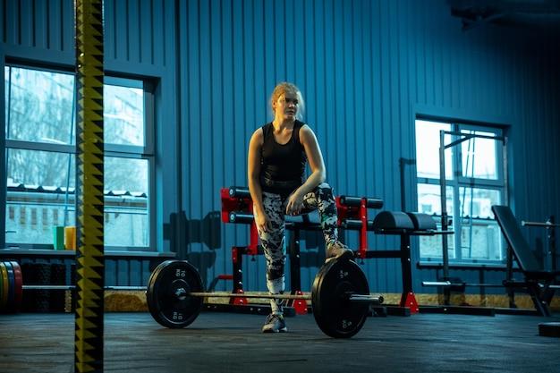 Кавказская девочка-подросток занимается тяжелой атлетикой в тренажерном зале
