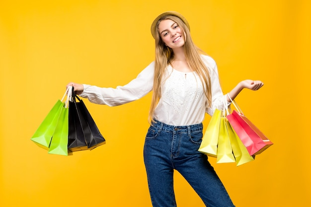 Caucasian teenage girl on yellow space. stylish young woman with shopping bags in hands