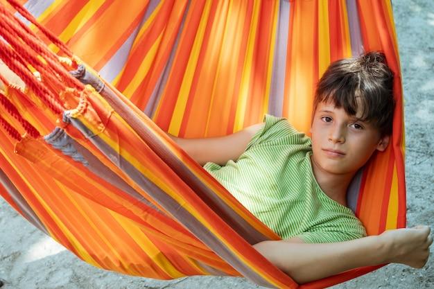 아이들을 위한 밝은 줄무늬 오렌지색 해먹 여름 활동적인 여가에서 휴식을 취하는 백인 십대 소년