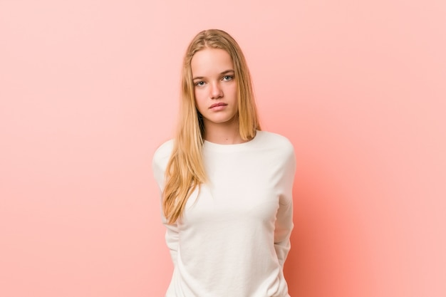 Caucasian teenager standing against a pink background
