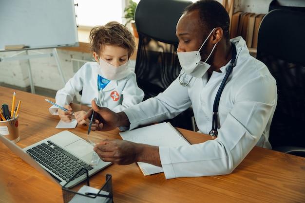 Adolescente caucasico come medico che consulta, dà consigli, cura. piccolo dottore durante la discussione, studiando con il collega più anziano. concetto di infanzia, emozioni umane, salute, medicina.
