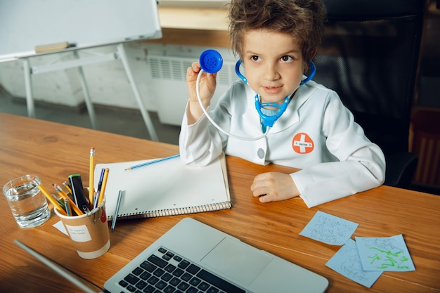 Caucasian teenboy as a doctor consulting for patient, giving recommendation, treating. little doctor during cheking the lungs, listening. concept of childhood, human emotions, health, medicine.