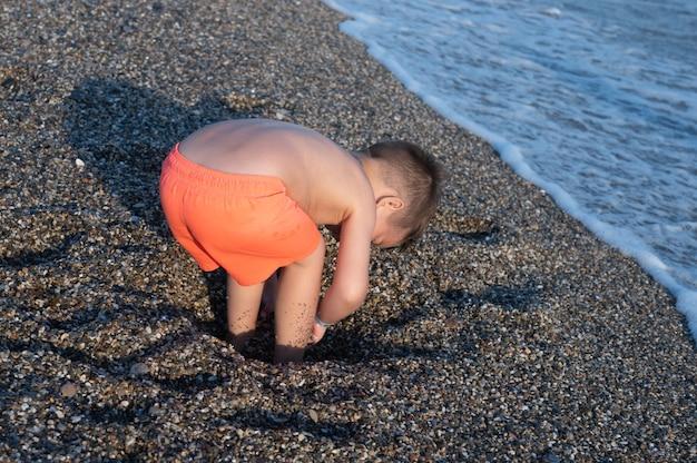 화창한 날 해변에서 노는 백인 유아 소년. 아이가 구멍을 파고 있습니다.
