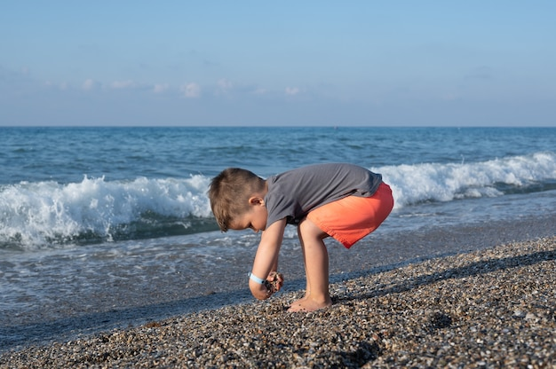 화창한 날 해변에서 노는 백인 유아 소년.