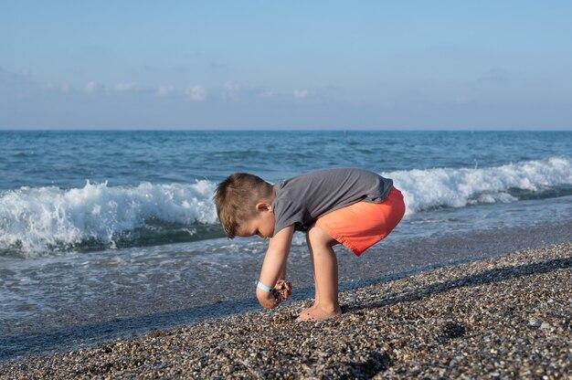 화창한 날에 해변에서 노는 백인 유아 소년.