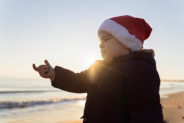 Caucasian toddler child in santa hat on the beach.