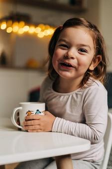 自宅でマグカップからココアを飲む白人の幼児の女の子。クリスマスボケライト。高品質の写真