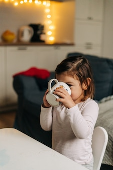 Caucasian toddler girl drinking cocoa from mug at home. christmas bokeh lights. high quality photo