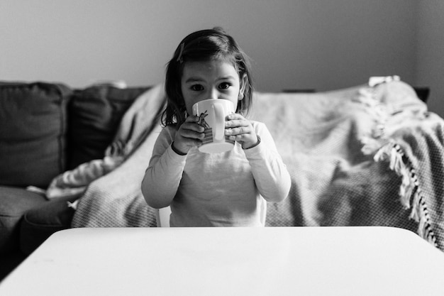 Caucasian toddler girl drinking cocoa from mug at home. christmas bokeh lights