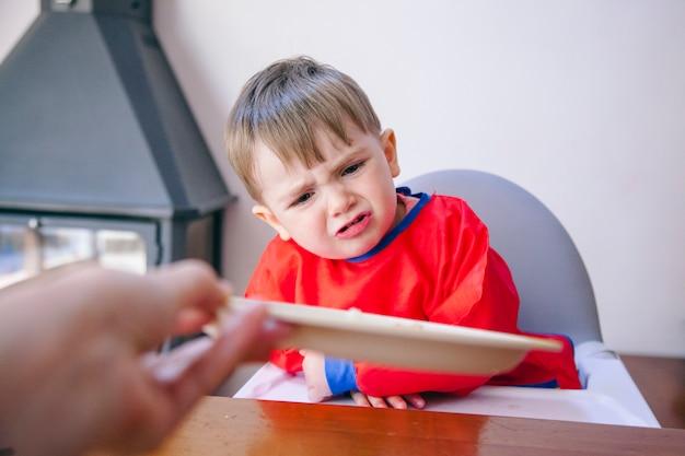 プレートから食べ物を食べることを拒否する白人の幼児。小さな子供を育てる行動の問題。