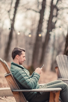 Caucasian tourist boy with cellphone outdoors in cafe. man using mobile smartphone.