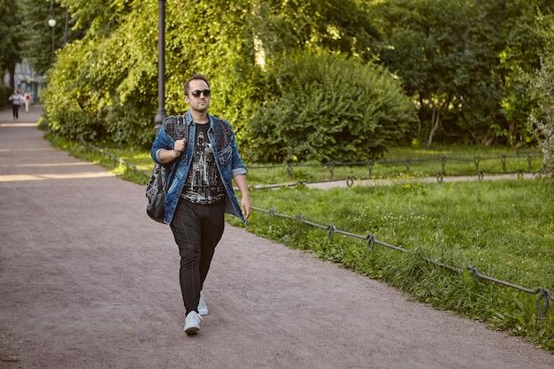 Кавказский турист в солнцезащитных очках и с рюкзаком гуляет на открытом воздухе.