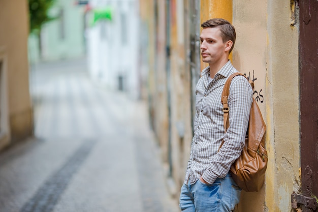 Caucasian tourist walking along the deserted streets of europe. young urban boy on vacation exploring european city