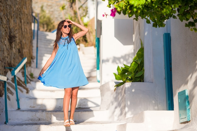 Caucasian tourist walking along the deserted streets of greek village. young beautiful woman on vacation exploring european city
