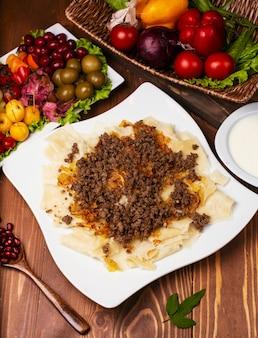 Кавказский традиционный форин хингал, хинкали. кавказская паста с мясом в белом фоне на деревянный стол.