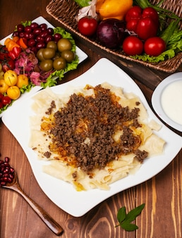 Caucasian traditional foor khingal, khinkali. caucasian pasta with meat in white plate on wooden table.