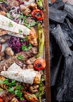 Caucasian traditional kebab platter with grilled foods and herbs.