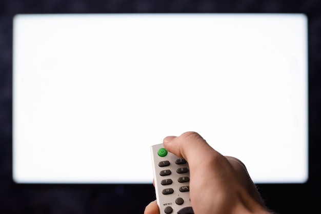 Caucasian tv viewer press green power button on a remote controller against a white blank empty screen