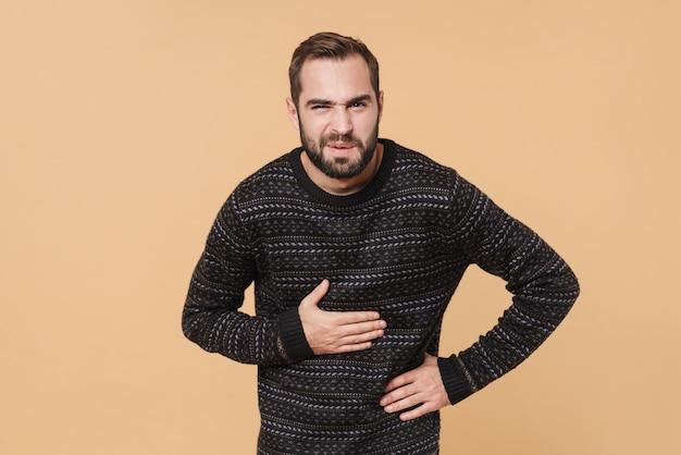 Кавказский небритый мужчина в зимнем свитере касается своего живота из-за боли, изолированной над бежевой стеной