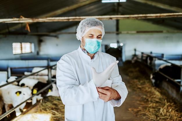 Кавказский ветеринар в защитной одежде надевает резиновые перчатки, стоя в конюшне